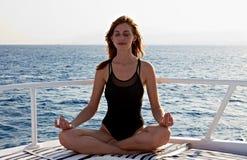 执行莲花凝思位置女子瑜伽年轻人 免版税库存照片
