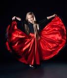 执行西班牙舞蹈的愉快的小女孩 库存照片
