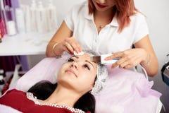 执行超声波面部削皮的妇女美容师对患者在美容院 库存图片