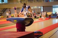 执行跃迁的年轻体操运动员女孩 免版税库存照片