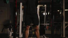 执行蹲坐的健身房的年轻肌肉人 股票录像