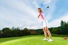 执行高尔夫球摇摆的路线的女性高尔夫球运动员 免版税库存照片