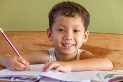 执行他的家庭作业的男孩 免版税库存照片
