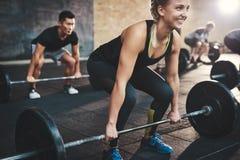 执行死的推力杠铃锻炼的妇女 免版税库存图片