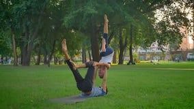执行acroyoga锻炼的年轻适合的女性和男性特写镜头射击在公园户外 影视素材