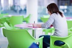 执行homeworkon校园的女性大学生 免版税图库摄影