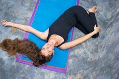 执行jathara parivarttanasa女子瑜伽的ardha 免版税库存图片