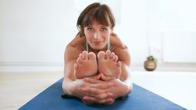 执行Paschimottanasana瑜伽姿势的美丽的妇女 图库摄影