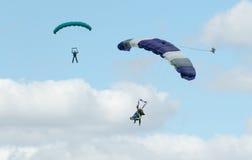 执行skydiving的两个跳伞运动员与降伞 免版税图库摄影