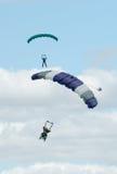 执行skydiving的两个跳伞运动员与降伞 免版税库存图片