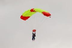 执行skydiving的跳伞运动员与降伞 免版税库存图片