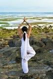 执行womang瑜伽年轻人的海滩 免版税库存图片