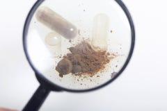 扩大化玻璃的看起来 棕色药片驱散在白色表面 一种有效成分从一个倾吐 免版税库存照片