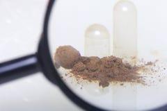扩大化玻璃的看起来 棕色药片驱散在白色表面 库存图片