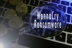 扩大化玻璃和硬币在键盘有ransonware攻击文本的 免版税库存照片
