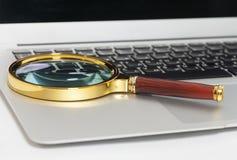 扩大化玻璃的膝上型计算机 免版税库存照片