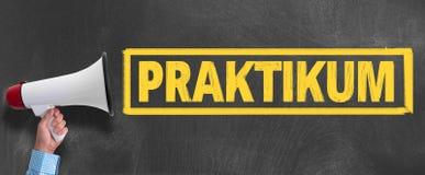 扩音机或手提式扬声机反对黑板有文本的PRAKTIKUM 图库摄影