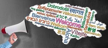 扩音机或手提式扬声机反对黑板有词的欢迎在许多不同的语言 免版税库存照片