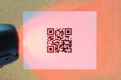 扫描QR在纸盒的代码标签有激光的 库存图片