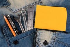 扭动在牛仔布工作者的工具有空白的便条纸的为文本、A牛仔裤有工程师工具的和便条纸 免版税图库摄影