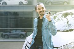 扭转他在经销商的年轻人新的汽车钥匙 免版税库存图片