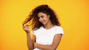扭转在手指,调情的人姿态的卖弄风情的微笑的mixed-race妇女卷毛 图库摄影