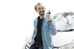 扭转在演播室的愉快的年轻人一把新的汽车钥匙 免版税库存图片