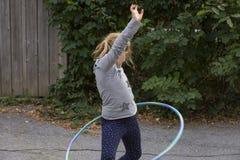 扭转她的臀部的小女孩,当使用与她的hula箍时 库存照片