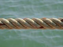 扭转的绳索,反对海的背景 库存照片