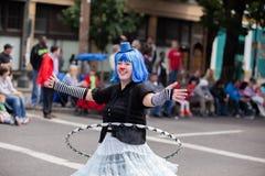 扮小丑与步行沿着向下街道的hula箍 免版税图库摄影