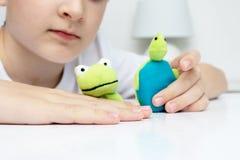 扮演不同的角色的一个白种人男孩通过使用手指木偶、玩具表现出的他的情感,侵略、恐惧和freandship 库存照片