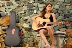 扮演俏丽的歌唱家的女性吉他 免版税图库摄影