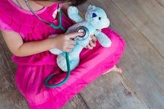 扮演医生或护士有长毛绒玩具熊的孩子顶视图在 库存照片