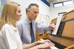 扮演女小学生教师的钢琴 图库摄影