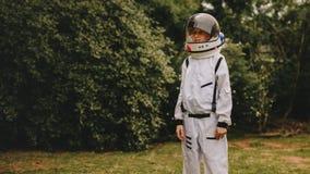 扮演宇航员的逗人喜爱的男孩在操场 免版税库存图片