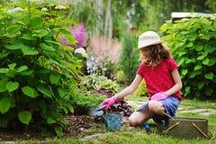 扮演小花匠和帮助在夏天庭院里的儿童女孩, 库存照片