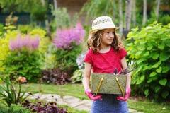 扮演小花匠和帮助在夏天庭院里的儿童女孩, 库存图片
