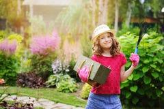 扮演小花匠和帮助在夏天庭院里的儿童女孩 图库摄影