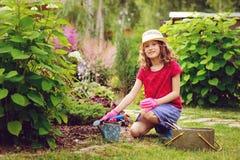 扮演小花匠和帮助在夏天庭院里的儿童女孩 免版税库存照片