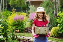 扮演小花匠和帮助在夏天庭院里的儿童女孩 库存照片