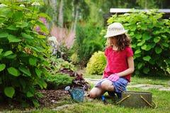 扮演小花匠和帮助在夏天庭院里的儿童女孩 库存图片