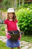 扮演小花匠和帮助在夏天庭院里的愉快的儿童女孩 图库摄影