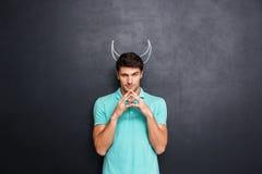扮演恶魔的角色严肃的人站立在黑板背景 免版税库存照片