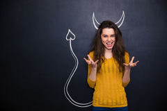 扮演恶魔的角色滑稽的妇女站立在黑板 免版税库存照片