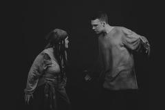 扮演戏剧的角色在黑暗的背景的一名年轻人和妇女 图库摄影