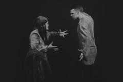 扮演戏剧的角色在黑暗的背景的一名年轻人和妇女 库存照片