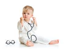 扮演有听诊器的严肃的孩子医生 免版税库存图片