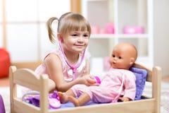 扮演有玩偶玩具的孩子医生 免版税库存图片
