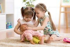 扮演有玩偶的两个儿童女孩医生 免版税库存图片