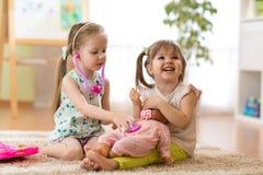 扮演有玩偶的两个孩子女孩医生 免版税库存照片